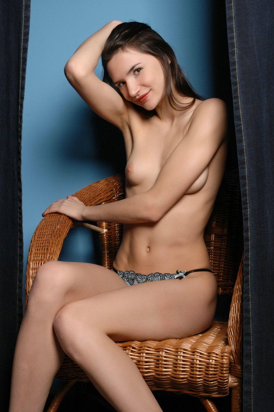 蓝色背景棚拍藤椅上的长头发名模